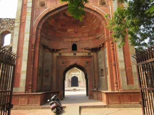 Brána:  Pohled z vnější strany mešity vidí zničené zdi, oblouky a klenby staveb, které sousedí s vysokou obvodovou stěnou mešity na obou stranách hlavní vstupní brány, která vede do nádvoří na východě. Tato červená pískovcová brána je většinou neporušená a její dvě mohutné pilíře vyčnívají mírně od obdélníkového půdorysu, aby podporovaly široký obloukový portál hluboko zapuštěný do plochého obdélníkového rámu. Tyto můstky jsou rozloženy na vnitřní ploše a vedou k menšímu, hluboce zapuštěnému klenutému vchodu. Jakmile je uvnitř, vidíme schody, které vedou k horní úrovni na obou stranách tohoto vchodu. Při pohledu z nádvoří je klenutý vchod také hluboce zapuštěn do širokého obloukového portálu na straně dvora.